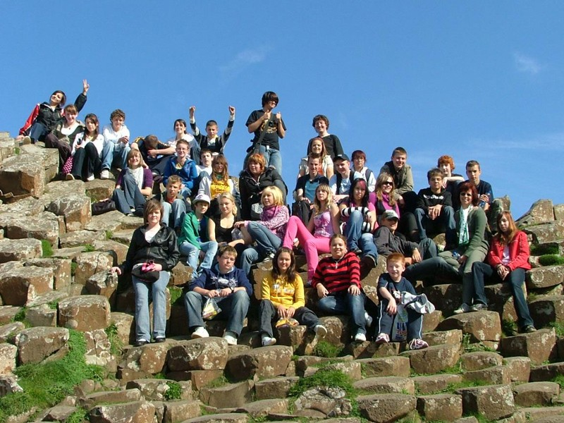 Many students gather on a sunny day for a photo at the Giant's Causeway