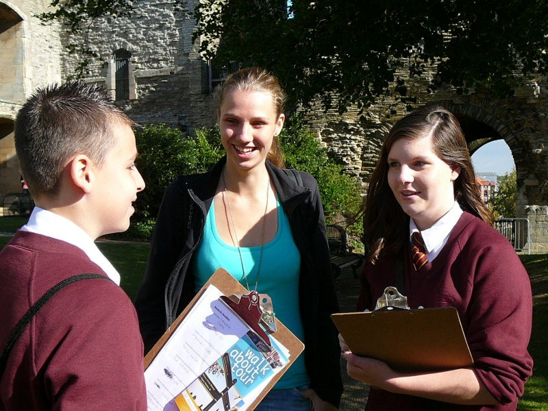 Three students are outdoors conducting an interview