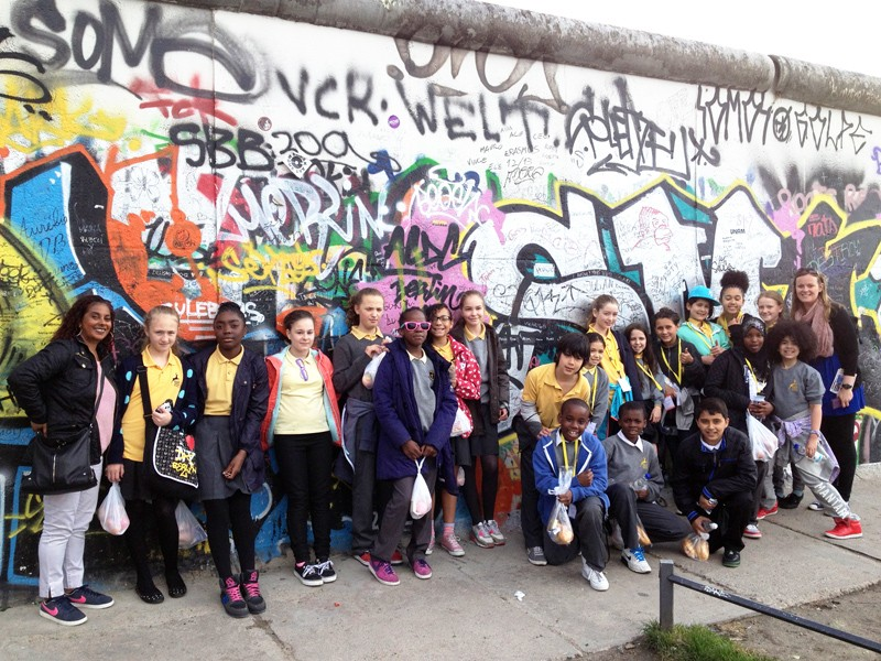 A large group of children pose for a photo in front of graffiti