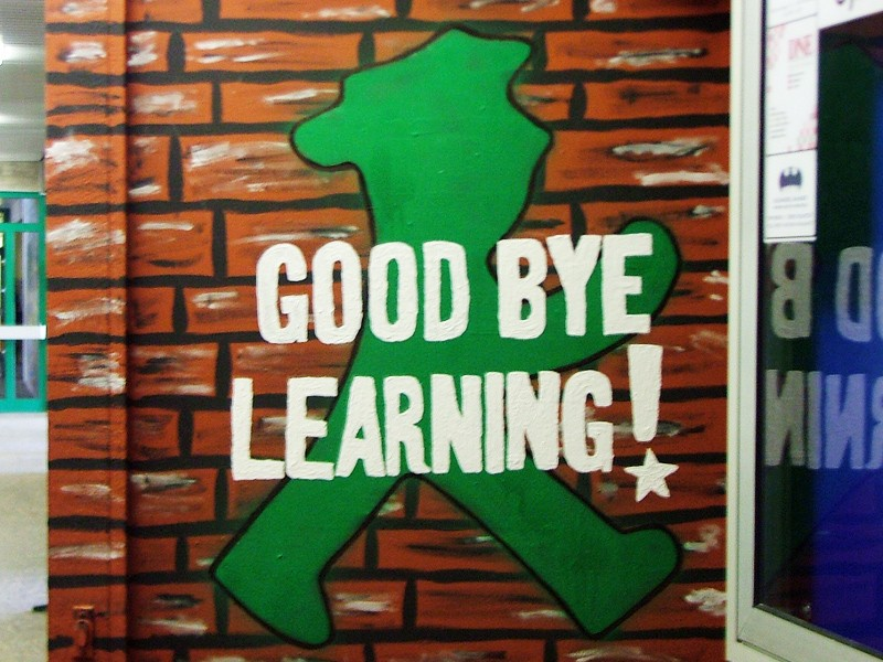 """A piece of wall art has the words """"good bye learning"""" overlaid onto a stylised green figure"""
