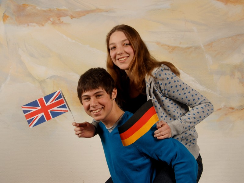 Girl being carried on boy's shoulders, in one hand she holds a German flag, in the other the UK flag