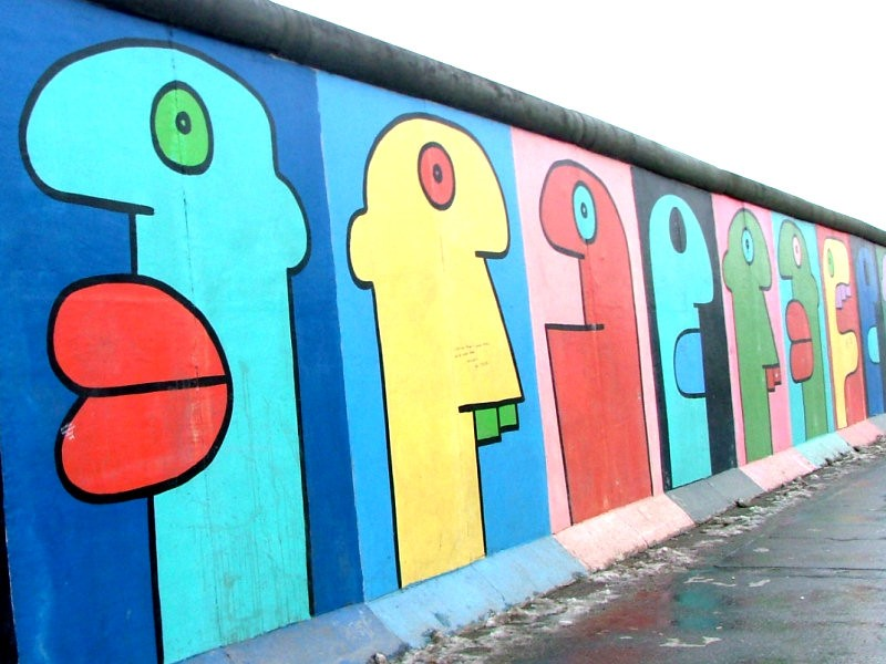 Colourful street art depicting a series of cartoonish faces