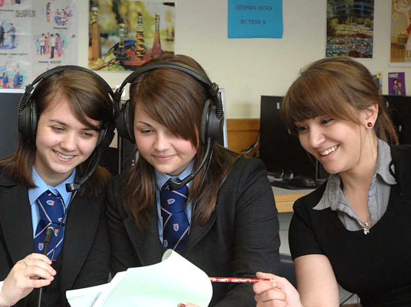 Studnets wearing headsets work alongside their teacher for some podcasting