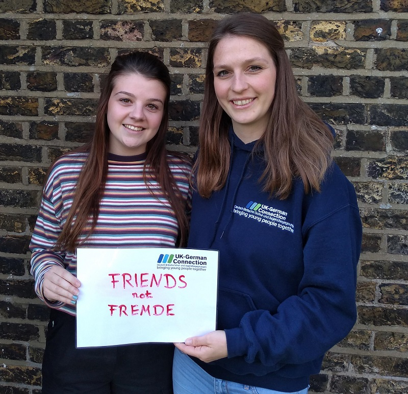 """Two people hold a sign which """"friends not fremde"""""""