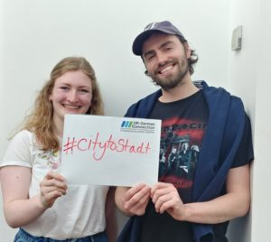 "Two people hold a sign which reads ""hashtag city to stadt"""