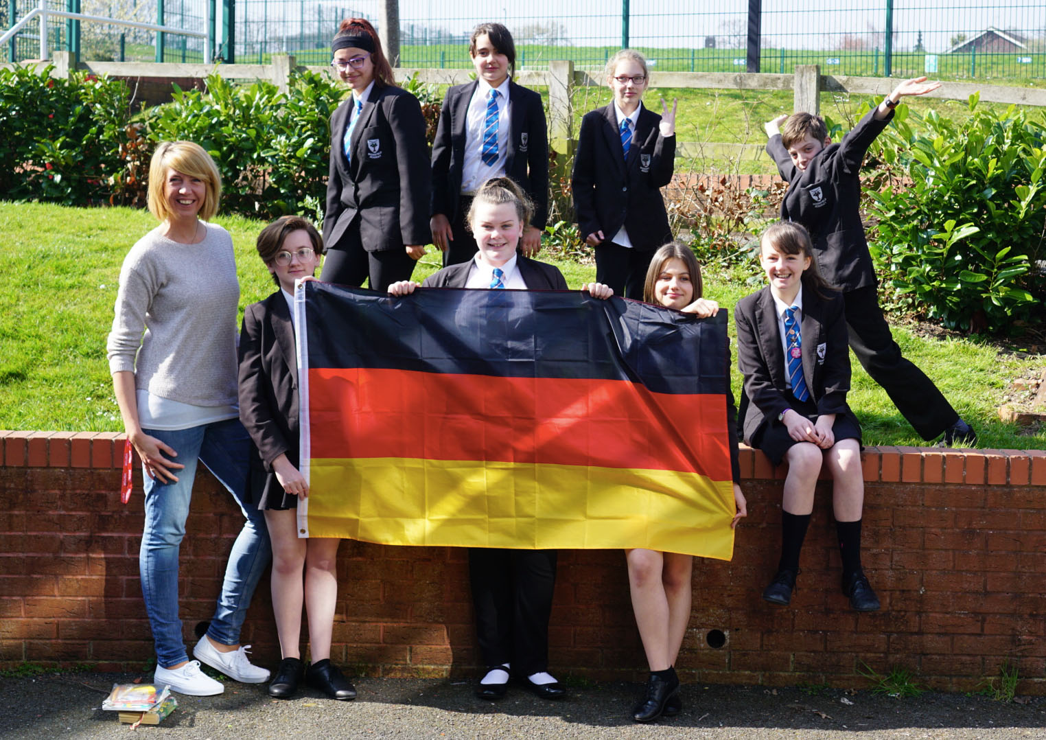 Students and and an adult posing for a photo, the students hold a German flag